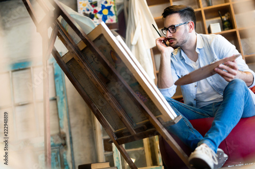 Portrait Of Male Artist Working On Painting In Studio - 222948819