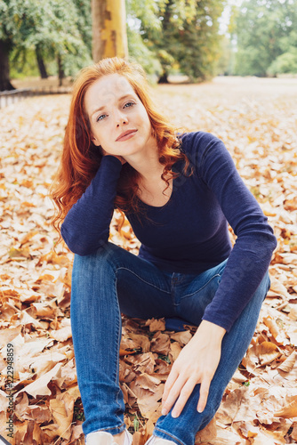 Leinwanddruck Bild Pretty young woman relaxing in an fall park