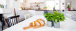benner with fresh basil and slices of bread on the table and kitchen interior unfocused in the background