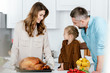 adorable little child preparing thanksgiving dinner with parents