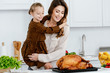 beautiful young mother and daughter embracing and looking at thanksgiving turkey