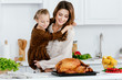 beautiful young mother and daughter embracing while cooking thanksgiving turkey together