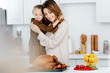 beautiful young mother and daughter embracing while cooking thanksgiving dinner together