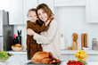 beautiful young mother and daughter embracing and looking at camera while cooking thanksgiving turkey together