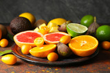 Plate with various delicious exotic fruits on color table