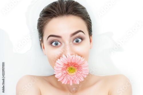 Portrait of funny beauty female woman adult with clean pure skin with pink flower taking spa relaxing in bath with white soap shampoo water. Skin beauty health care concept. Body part bare shoulder © Monstar Studio