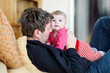 Leinwanddruck Bild - Happy proud young father with newborn baby daughter, family portrait together