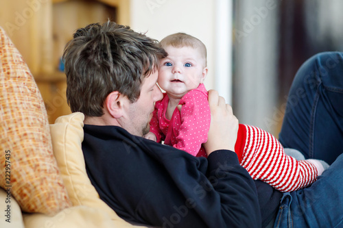 Leinwanddruck Bild Happy proud young father with newborn baby daughter, family portrait together