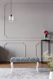Grey hallway interior with a bench, lamp and flower in a vase on a stand. Real photo. Place for your poster - 222965033