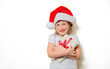 Portrait of an emotional toddler girl in Christmas hat with gift box on white background