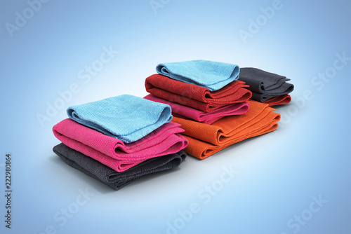 Pile of colored towels isolated on blue gradient background 3d