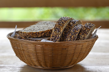 Basket with slices of bread with seeds on the table