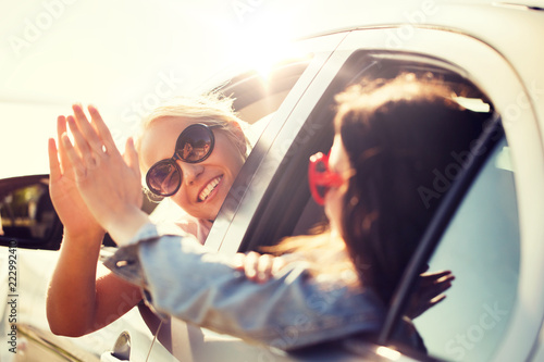 Leinwandbild Motiv summer vacation, holidays, travel, road trip and people concept - happy teenage girls or young women in car at seaside making high five gesture