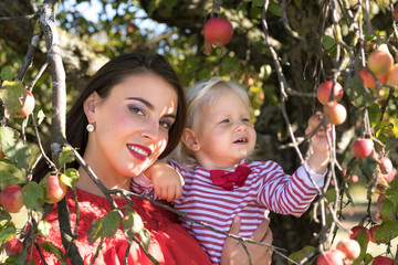 Mother with little daughter in an apple orchard