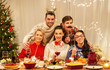 holidays and celebration concept - happy friends with party props having christmas dinner at home