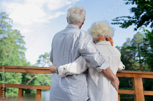 Observing nature. Peaceful loving senior couple hugging and enjoying the nature while looking at the river - 222998419