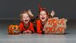 happy Halloween! cheerful children in costume with pumpkins on grey background
