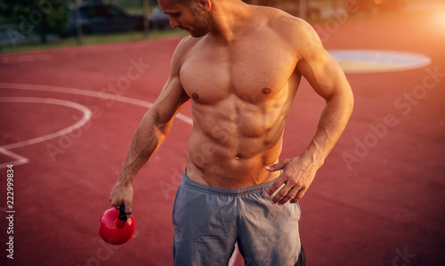 Wall mural Handsome man working exercises in early morning with sunrise. Fitness training outdoors.