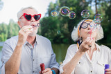 Soap bubbles. Funny active couple of pensioners standing on the bridge and blowing soap bubbles - 223000066