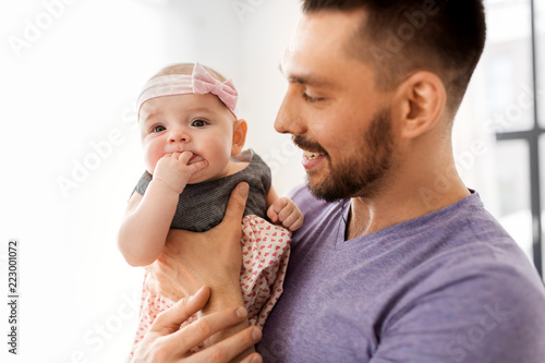 Leinwandbild Motiv family, fatherhood and people concept - close up of father with little baby girl at home