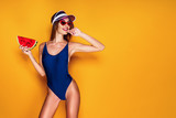 Beautiful young lady in swimwear biting finger and holding piece of fresh watermelon while standing on yellow background. Sopy space - 223003610