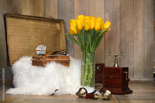 Leinwandbild Motiv A bouquet of yellow tulips in a vase in the interior of a retro