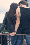 back view of stylish couple embracing near railings on roof - 223011673