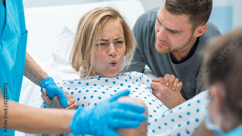 Leinwanddruck Bild In the Hospital Woman in Labor Pushes to Give Birth, Obstetricians Assisting, Husband Holds Her Hand for Support. Modern Delivery Ward with Professional Midwives.