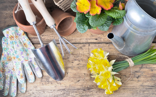 Sticker gardening arrangement with tools and flowerpot on a wooden table