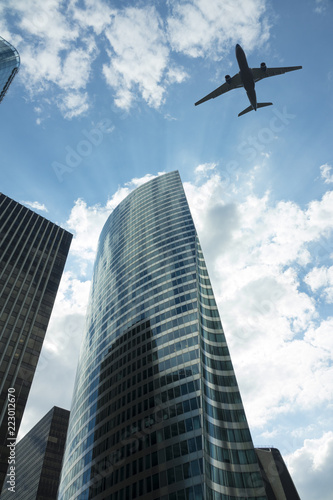 Fototapeta Airplane in the sky with modern buildings