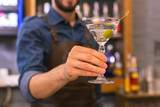 Tasty alcohol. Careful professional barman holding a glass of delicious alcohol with an olive - 223013699