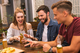 Counting. Positive young friends feeling interested and having fun while playing games in the bar - 223016029