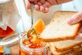 female hand smears toasts with homemade orange jam - 223027649