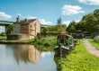 A converted canal narrowboat acts as a tearoom with a small outdoor garden seating area on the Leeds Liverpool Canal, near Wigan