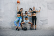 Fitness women in cheerful mood standing against a wall outdoors