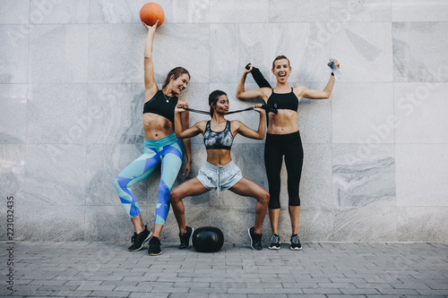 Fitness women in cheerful mood standing against a wall outdoors - 223032435