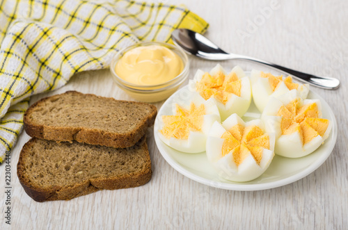 Boiled chicken eggs in saucer, mayonnaise, napkin, bread and spoon © Evgeny