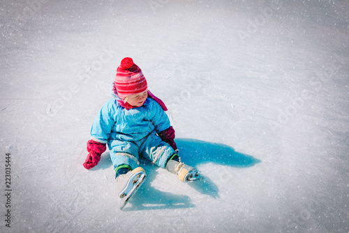 Leinwanddruck Bild cute little girl sitting on ice with skates after the fall