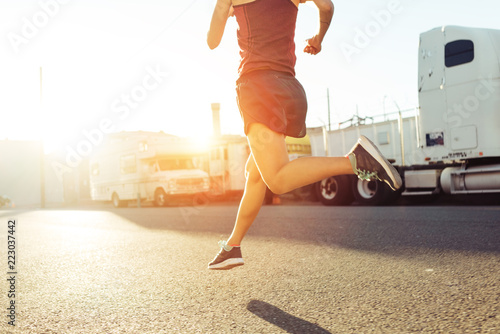Young woman running on the city street in the evening, sunset time