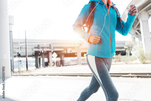Wall mural Sporty woman running in city industrial area