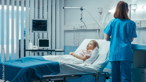 Leinwanddruck Bild Sick Little Girl Lies on a Bed In the Hospital. Cute ill Child is Taken Care of by Nurse in the Modern Pediatric/ Children Ward.