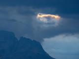 Schwebender Ring aus Feuer vor dunkelblauen Wolken über Gipfeln der Dolomiten, Südtirol, Italien