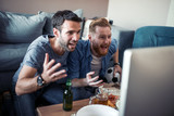 Friends enjoy the football game on TV - 223047062