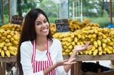 Latin american saleswoman at farmers market presenting bananas - 223050655