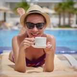 Beautiful European girl in a sunhat is laying on the sunbed at the hotel near the pool. She is having a rest, holding cup of coffee in her arms and smiling to the camera. - 223051206