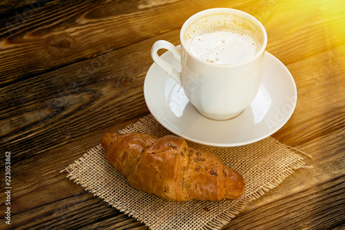 Rural French. Cup of hot coffee and a croissant on a wooden table