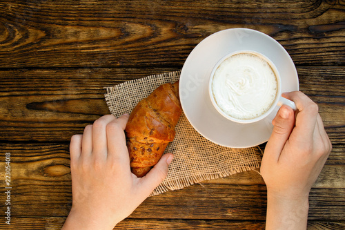 hand taking a croissant from the table where there is a Cup of coffee with whipped cream