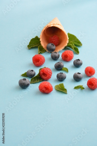 Foto Murales An ice cream cone with blueberries, raspberries and mint on a colorful background as a symbol of a refreshing summer fruity ice cream