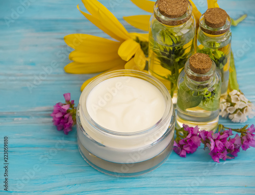esencja kosmetyczna, kosmetyk, olej, kwiaty na drewnianym tle