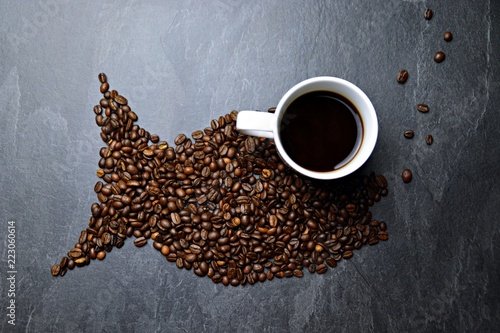 Coffee beans on a black background form the silhouette of a whale and two cups of coffee form their eyes - concept with coffee and whale